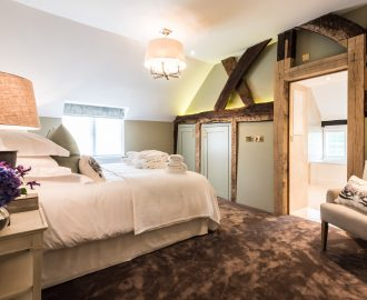 Beamed family bedroom with luxury flooring
